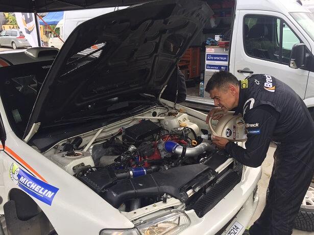 Krzysztof Hołowczyc wlewa olej do swojego Subaru Impreza